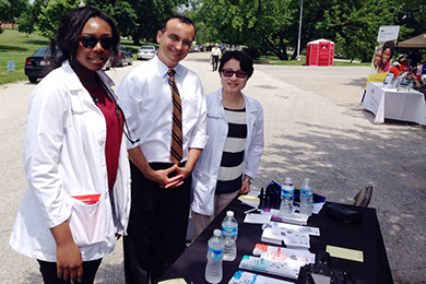 Dr. Daniel Mansour appears at a health fair alongside two other members of the Lamy Center team.