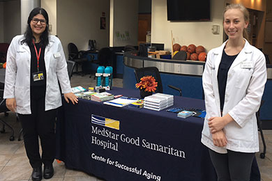 Two trainees pose next to a table in the Center for Successful Aging at MedStar Good Samaritan Hospital.