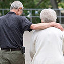 Elderly man standing next to elderly woman with arm draped across her shoulders.